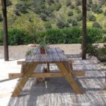 Rustic table under the shade hurdle located between the house and pool